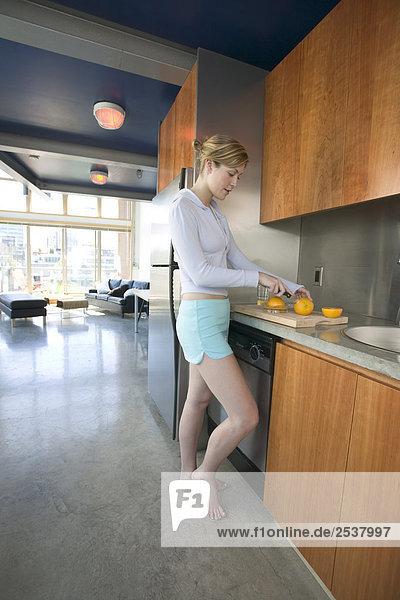 Frau schneiden Orange in Loft  Vancouver  British Columbia