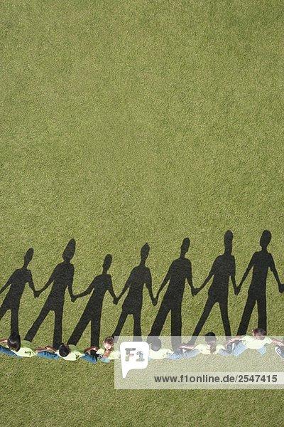 Schatten Sie auf Gras hält hände Kinder
