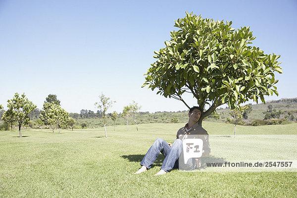 Mann im Schatten unter Baum sitzen