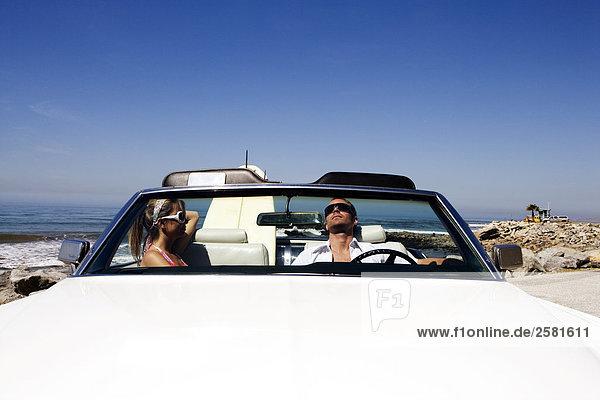 Paar entspannenden im geparkten Auto am Strand