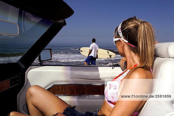 Frau beobachtet  wie Man in Richtung Strand mit Surfboard walks