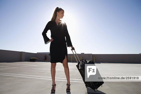 Frau stehend mit Gepäck
