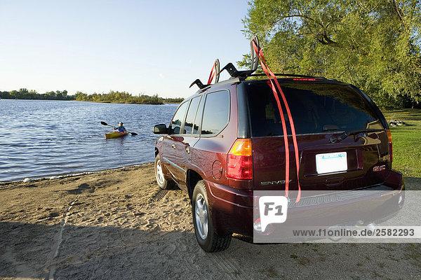 GMC Envoy geparkt See mit Kajakfahrer im Hintergrund