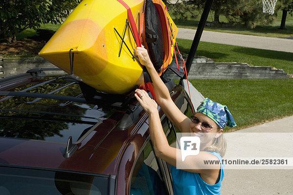 Frau lädt Kajak zu Anfang der SUV in Einfahrt