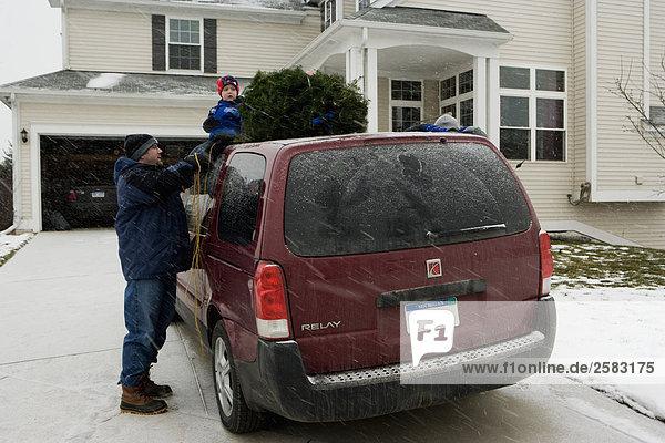 Dach nehmen Menschlicher Vater Sohn Auto Hilfe Weihnachtsbaum Tannenbaum
