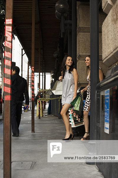 Frau tragen Tasche Gebäude kaufen 2 jung aussteigen