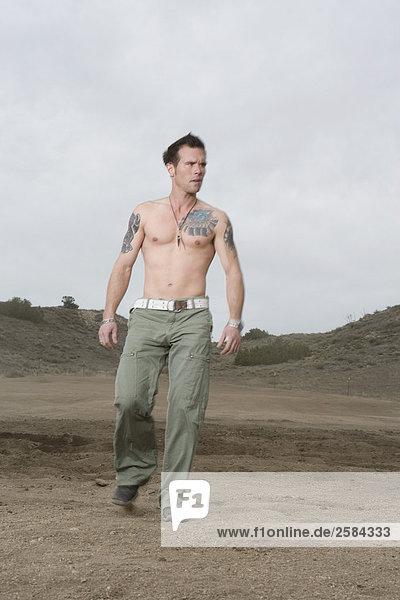 Mann mit Tätowierungen geht in Richtung Kamera in California-Wüste