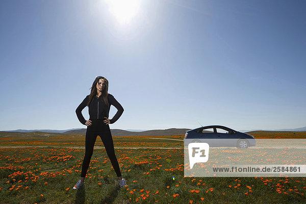 Junge Frau im orange Mohnfeld mit Händen auf Hüfte
