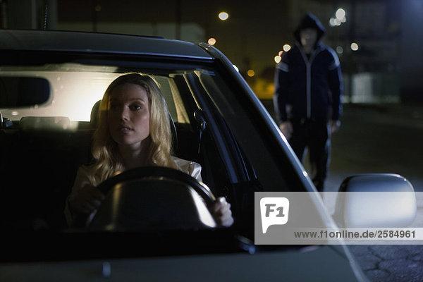 Frau in SUV Ansichten ein Prowler in Rear View Mirror in der Nacht