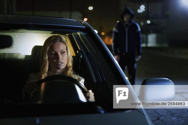 Frau in SUV sieht eine Prowler in Flügel Spiegel in der Nacht