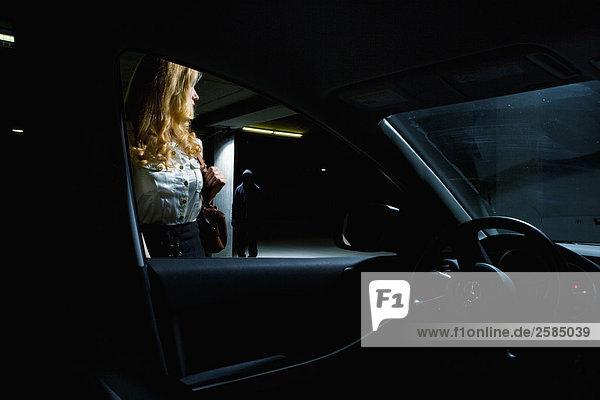 Frau Auto nähert und sieht Prowler im Hintergrund