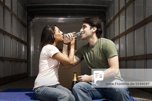 junges Paar Sitting auf der Rückseite des beweglichen LKW Champagner trinken