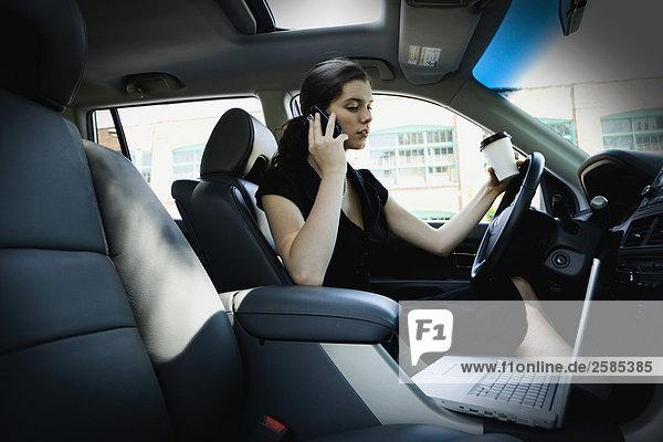 Junge Frau auf Handy während der Fahrt