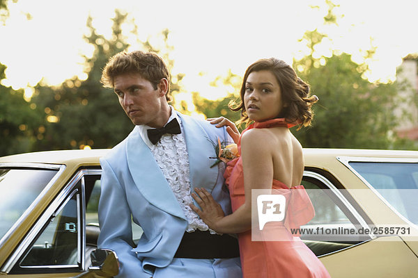 Young couple by car going to prom