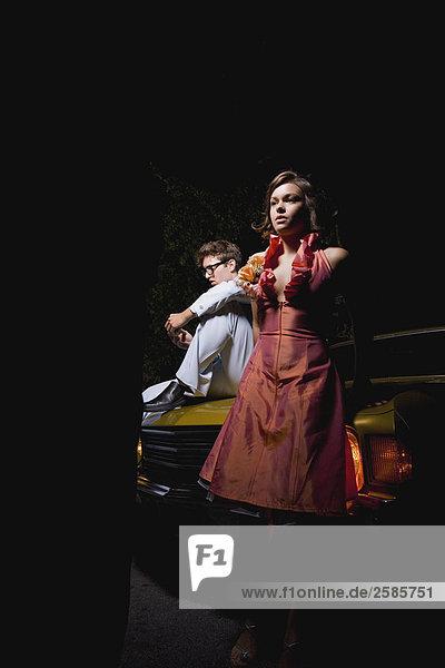 PROM Paar steht von Front des Autos
