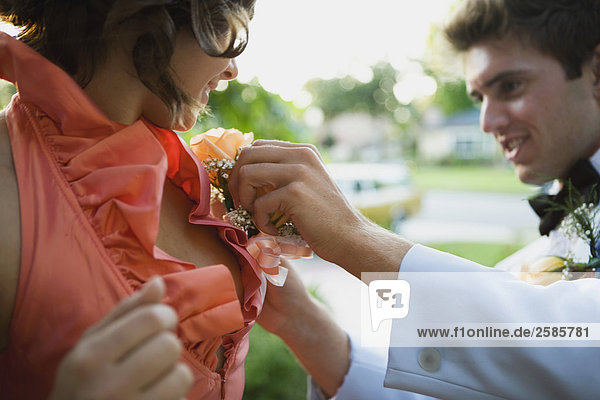 Young man helping with young woman's corsage