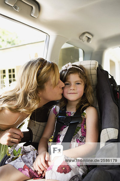 Mother kissing daughter sitting in child seat in car