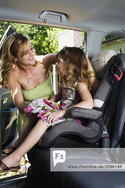 Mutter mit jungen Mädchen in Auto-Kindersitz
