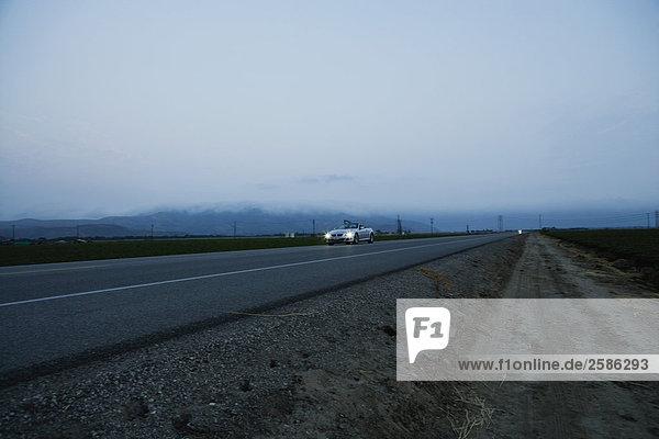 Paar fahren BMW 650i durch Felder