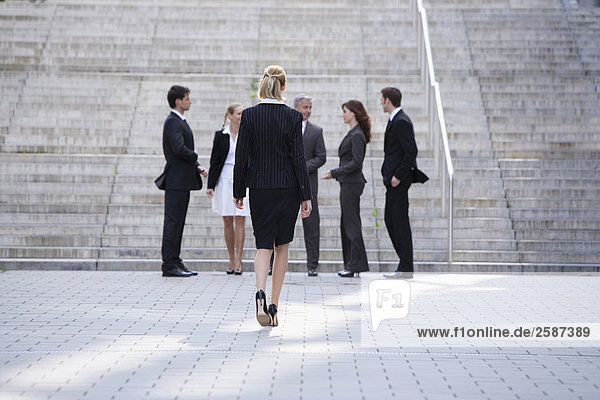 Businessswoman walking  businesspeople waiting in background
