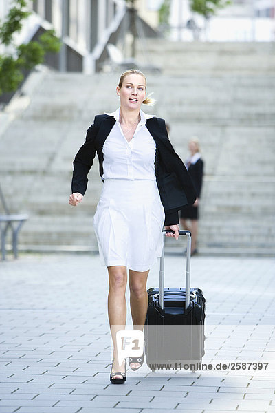 Businesswoman walking with case  in a hurry