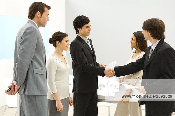 Geschäftsfreunde treffen sich  schütteln sich die Hände  während andere zusehen.