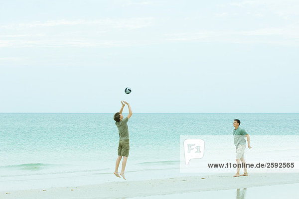 Two men playing volleyball on beach