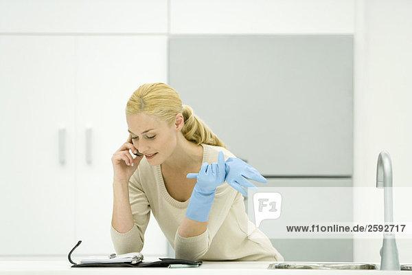 Frau in Gummihandschuhen an der Küchenzeile lehnend  mit dem Handy  auf die Agenda schauend