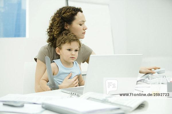 Frau sitzt am Schreibtisch mit Kleinkind auf dem Schoß  legt Festnetztelefon auf.