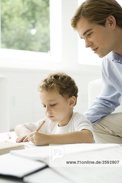 Vater hilft dem jungen Sohn bei den Hausaufgaben