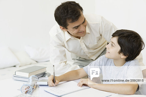 Father helping son with homework  both smiling at each other