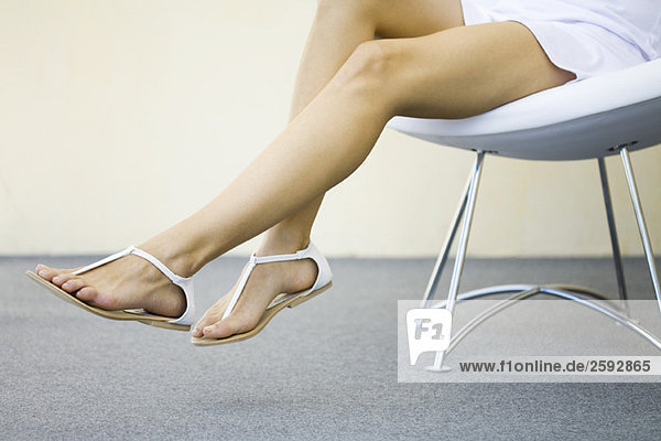 Woman sitting in chair with legs dangling  wearing sandals  cropped view