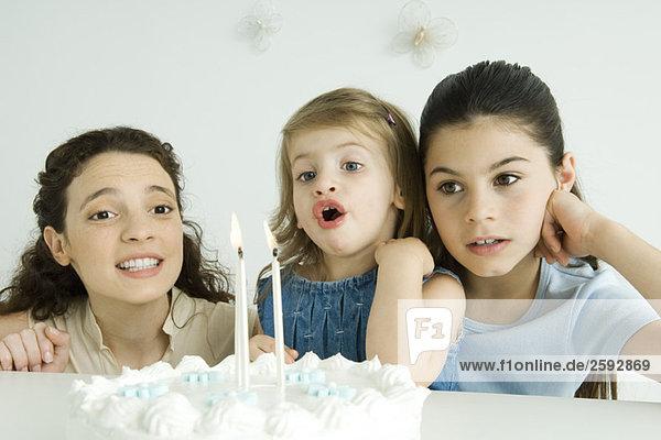 Kleines Mädchen beim Ausblasen von Kerzen auf Geburtstagskuchen  Mutter und ältere Schwester beim Zuschauen