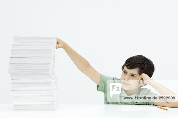 Boy sitting with tall stack of papers  holding head  frowning