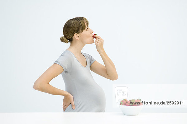 Pregnant woman eating strawberries  side view