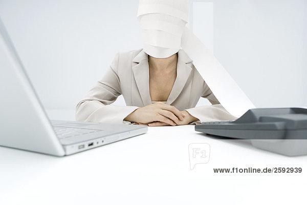 Professionelle Frau am Schreibtisch sitzend  Papier von der Addiermaschine um das Gesicht gewickelt