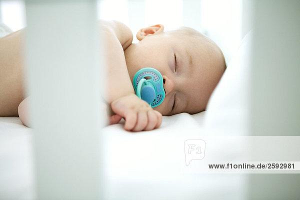 Baby schläft im Kinderbett  Schnuller im Mund Baby schläft im Kinderbett, Schnuller im Mund