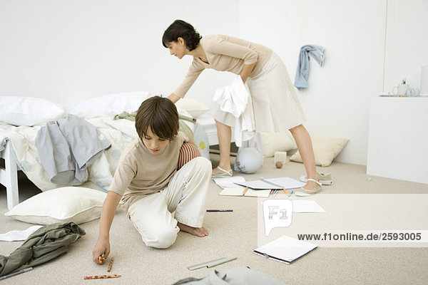Mother helping boy clean messy room  full length