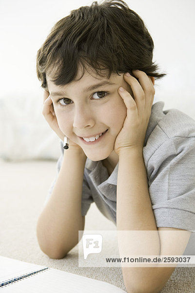 Boy lying on the ground with notebook  holding head  smiling at camera