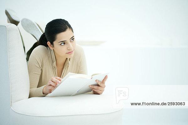 Junge Frau auf dem Bauch auf dem Sofa liegend  Buch haltend  wegschauend