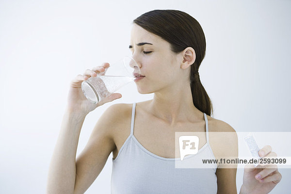 Frau trinkt Brausewasser  hält Arzneipäckchen in der Hand