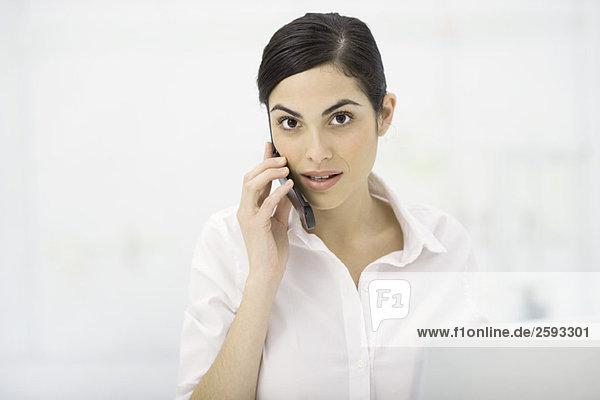 Frau spricht auf dem Handy  schaut in die Kamera