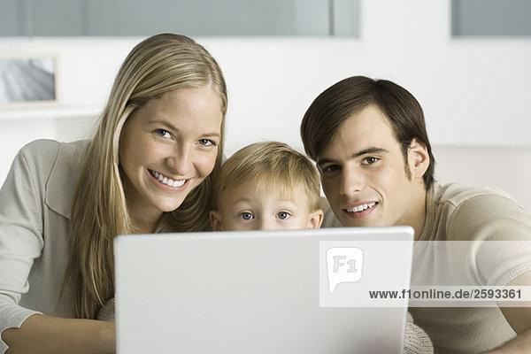 Eltern und junger Sohn mit Laptop-Computer  lächelnd vor der Kamera
