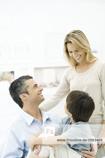 Familie lächelt sich an  Junge sitzt auf dem Schoß des Vaters.