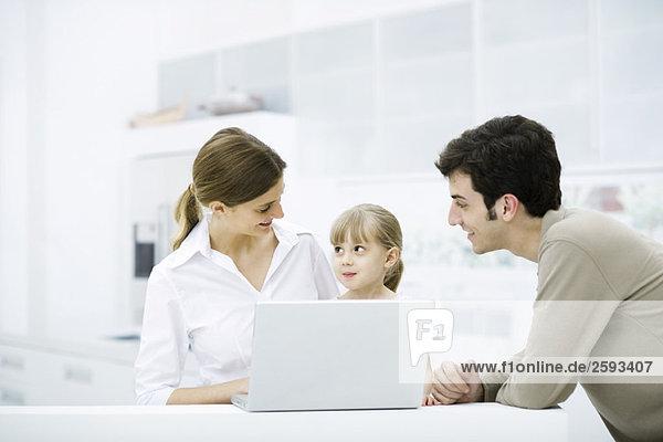 Familie versammelt um Laptop-Computer  lächelnd  Mädchen sucht Mutter
