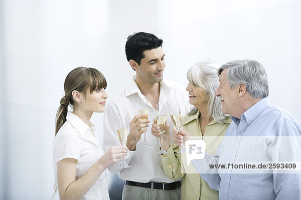 Paar stehend mit älteren Eltern  alle mit Champagnerflöte