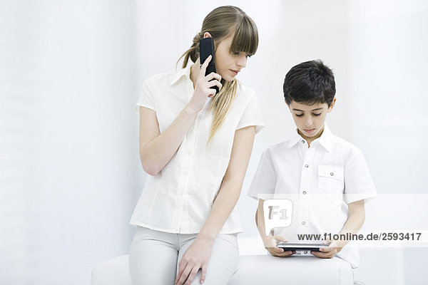 Woman using cell phone  watching boy play handheld video game