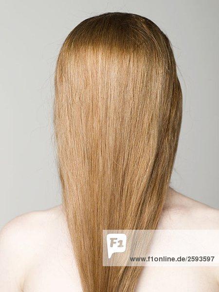 Eine junge nackte Frau mit ihren Haaren  die ihr Gesicht bedecken.