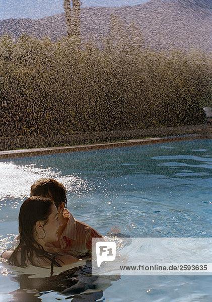 Ein junges Paar  das sich im Schwimmbad umarmt.
