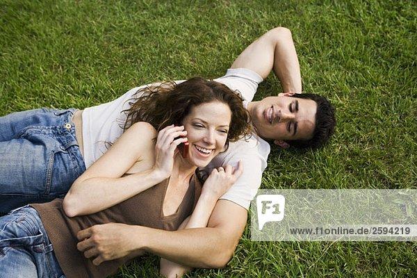 Ein junges Paar  das sich auf einem Rasen kuschelt.